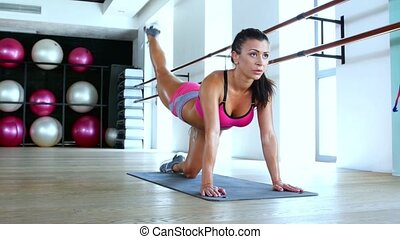Young beautiful fitness girl exercising in the gym Dolly...