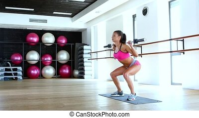 Girl squats in the gym, woman trains in gym, healthy young...