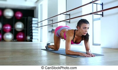 Healthy young woman working out in gym, sports girl involved...