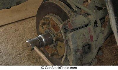 Mechanic Dismantling Brake Disk Of Car - CLOSE UP of...
