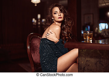 Beauty young brunette woman sitting at the bar with glass of...