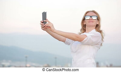 Beautiful girl in sunglasses doing a self-portrait on the...