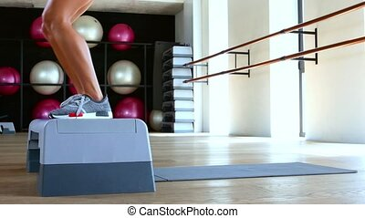 Woman doing step jumps at the gym. Dolly shot - A woman...