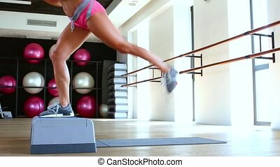 Exercise with step jump. Dolly shot - Woman doing step jumps...
