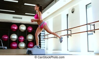 Exercise with step in gym, woman doing step jumps at the...
