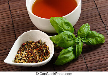 close up of cup of tea with tea leaves and basil leaves on a...