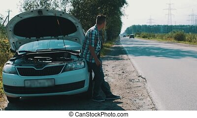 Man stay at broken car with opened capote at road. Come to...