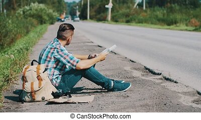 Man sit at road in countryside. Hitchhiking. Waiting. Looking map. Sunny day