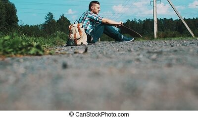Young man sit at road in countryside with cardboard plate. Hitchhiking. Problem