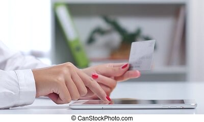 Woman buying online with a silver credit card and tablet. Close up