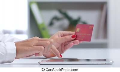 Woman finish up online shopping paying with a card through the tablet. Close up
