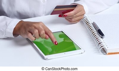 Woman doing an online purchase with credit card and tablet. Close up