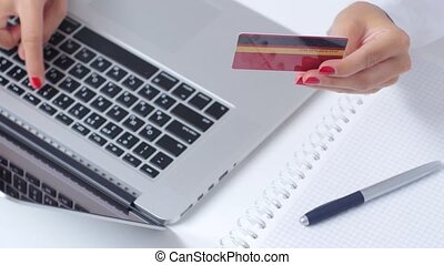 Woman with card in hand completes online shopping through...