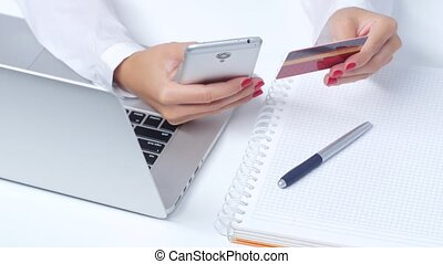 Girl doing shopping online via mobile and credit card. Close up