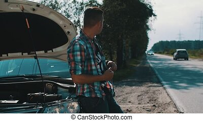 Upset man at broken car with opened capote at road in...