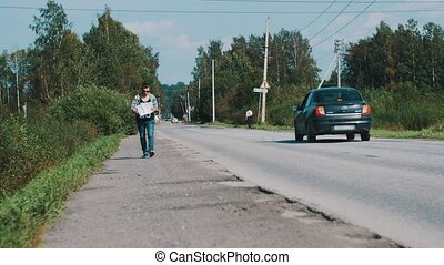 Man walk along the road in countryside with map in hands. Hitchhiking. Cars.