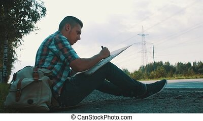 Man sit at road in countryside write on cardboard plate. Hitchhiking. Problem.