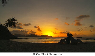 elderly couple enjoying a tropical sunset wide