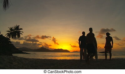 get together in the sunset - four tourists meeting for chat...