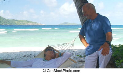 senior couple relaxing under palmtrees - happy senior couple...