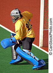 A field hockey goalie readies to protect the goal.