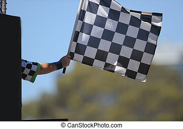 Chequered Flag - A chequered flag being waved on a raceway.