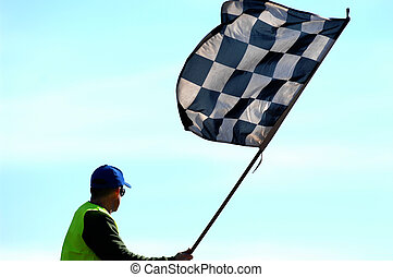 A checkered flag being waved at the completion of a race