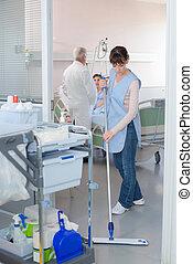Cleaner sweeping floor in hospital