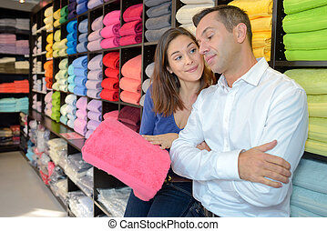 Woman trying to convince man to buy pink towel