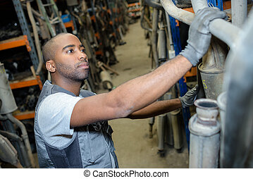 Man selecting used exhaust pipe