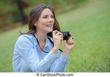 Woman in park taking photograph