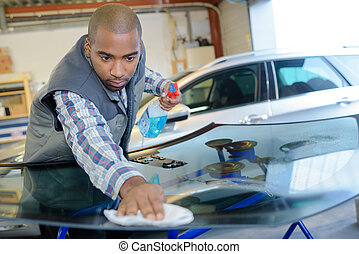 Garage worker polishing replacement windscreen