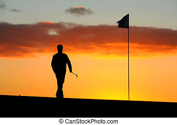 Morning golfer - a male golfer goes to remove the flag...