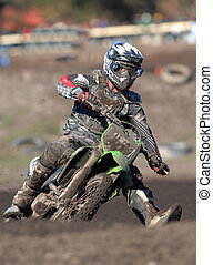 A muddy motocross rider in action during a race