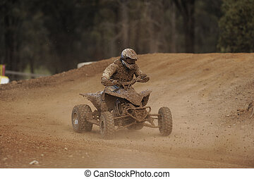 ATV racing - A muddy ATV racer takes a turn during a race.