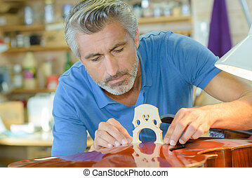 Musical instrument maker affixing bridge to cello