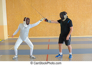 People fencing indoors