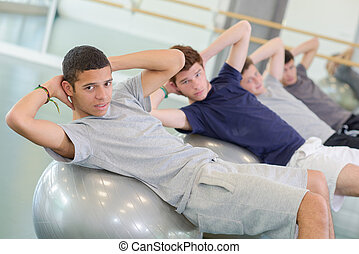 men on top of gym ball
