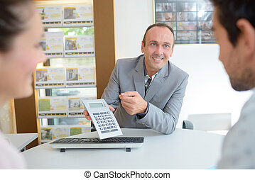 couple negotiating offer in estate agents