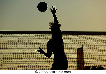 A female beach volleyball player spikes the ball over the...