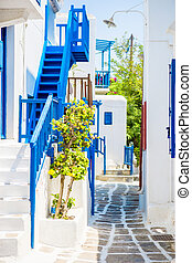 The narrow streets of the island with blue balconies, stairs and flowers. Beautiful architecture building exterior with cycladic style.