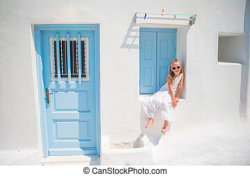 Charming girl in white dress outdoors in old streets an...