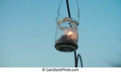 Glass Jar Candle Hanging on Arch Slow Motion.