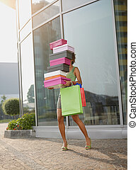 woman carrying shoe boxes - hispanic woman balancing stack...