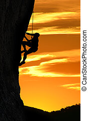 Silhouette of a climber over beautiful sunset - Man rock...