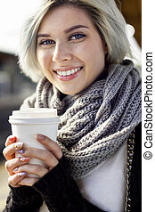 Happy Woman Holding Disposable Coffee Cup At Train Station -...