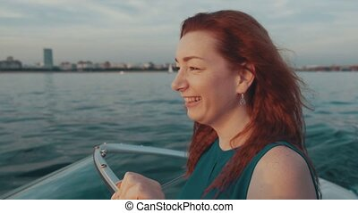 Happy red hair girl in turquoise dress sail on motor boat....