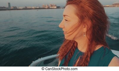 Red hair girl in turquoise dress sail on motor boat...