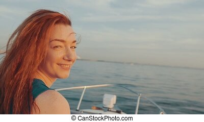 Happy red hair girl in turquoise dress steer motor boat...