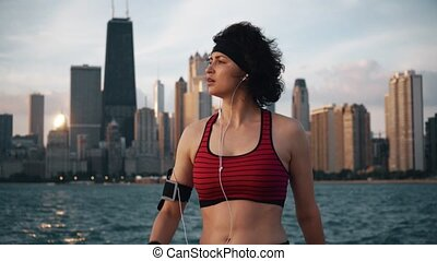 Runner athlete stands on the background of skyscrapers and seaside